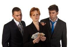 Geschäftsfrau, die Geld mit Kollegen zählt stockfotografie
