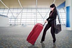 Geschäftsfrau, die Gepäck im Flughafen zieht Stockbilder