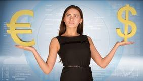 Geschäftsfrau, die Golddollar- und -Eurozeichen hält Stockfotos