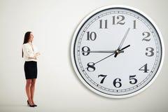 Geschäftsfrau, die große weiße Uhr betrachtet Stockfotos