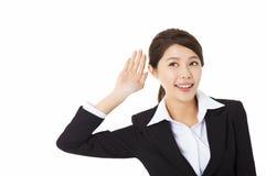 Geschäftsfrau, die Hand zum Ohr und zum Hören setzt Stockfoto
