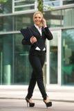 Geschäftsfrau, die am Handy außerhalb des Büros spricht Stockfotografie