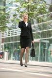 Geschäftsfrau, die am Handy in der Stadt geht und spricht Lizenzfreie Stockfotografie