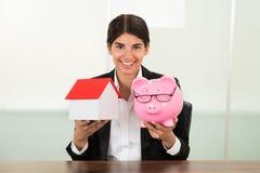 Geschäftsfrau, die Haus Modell und piggybank hält Stockbild