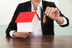 Geschäftsfrau, die Hausmodell und -schlüssel hält Stockfotos
