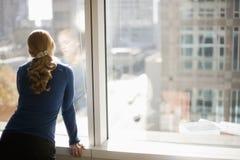 Geschäftsfrau, die heraus Bürofenster schaut Lizenzfreie Stockfotos