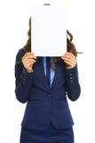 Geschäftsfrau, die hinter Blatt des leeren Papiers sich versteckt Lizenzfreies Stockfoto