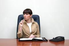 Geschäftsfrau, die hinter dem Schreibtisch im Büro, das Problem lösend sitzt Lizenzfreie Stockfotos