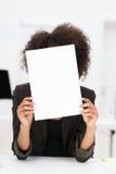 Geschäftsfrau, die hinter einem leeren Blatt Papier sich versteckt Lizenzfreie Stockbilder