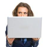 Geschäftsfrau, die hinter Laptop sich versteckt Lizenzfreie Stockfotografie