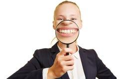 Geschäftsfrau, die hinter Lupe lächelt lizenzfreies stockbild
