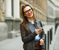 Geschäftsfrau, die hinunter die Straße bei der Unterhaltung auf intelligentem pho geht Lizenzfreie Stockbilder