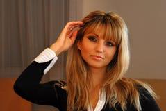 Geschäftsfrau, die ihr blondes Haar vor dem Spiegel handhabt Lizenzfreie Stockbilder