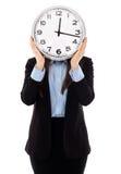 Geschäftsfrau, die ihr Gesicht mit einer Uhr bedeckt Lizenzfreie Stockbilder