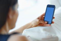 Geschäftsfrau, die ihr Smartphone im Büro verwendet Stockfotografie