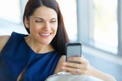Geschäftsfrau, die ihr Smartphone im Büro verwendet Lizenzfreies Stockbild
