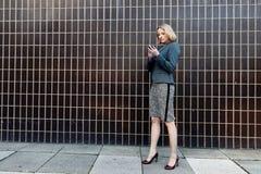 Geschäftsfrau, die ihr Telefon überprüft stockbild