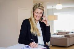 Geschäftsfrau, die ihr Telefon verwendet und Anmerkungen macht Stockfotografie