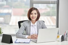 Geschäftsfrau, die ihre Laptop-Computer im Büro verwendet JPG + vektorabbildung lizenzfreie stockfotografie