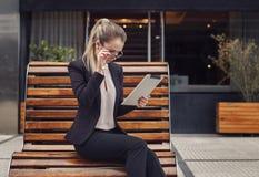 Geschäftsfrau, die ihre Tablette überrascht betrachtet Stockfotografie