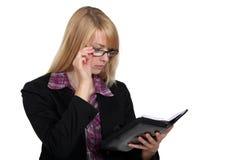 Geschäftsfrau, die ihre Tagesordnung betrachtet Lizenzfreie Stockfotografie