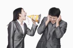 Geschäftsfrau, die an ihrem Kollegen durch Parteihut schreit Stockfoto