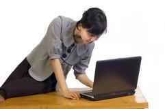 Geschäftsfrau, die ihrem Laptop ernst betrachtet Lizenzfreie Stockfotografie