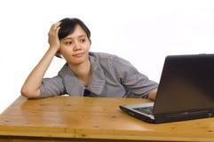 Geschäftsfrau, die ihrem Laptop ernst betrachtet Stockbild