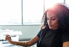 Geschäftsfrau, die an ihrem Schreibtisch im Büro arbeitet Lizenzfreies Stockfoto