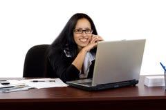 Geschäftsfrau, die an ihrem Schreibtisch mit einem Laptop arbeitet Lizenzfreie Stockfotos