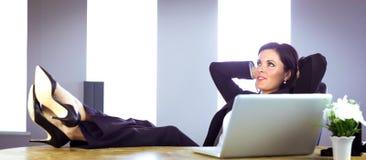 Geschäftsfrau, die an ihrem Schreibtisch sich entspannt Stockbild