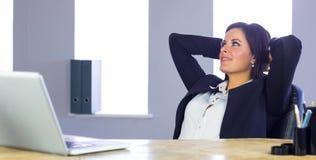 Geschäftsfrau, die an ihrem Schreibtisch sich entspannt Stockfoto