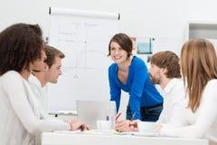 Geschäftsfrau, die ihrem Team eine Darstellung gibt Stockfoto