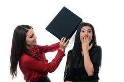 Geschäftsfrau, die ihren Kollegen mit einem Laptop schlägt Stockfotos