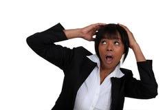 Geschäftsfrau, die ihren Kopf abschirmt Stockbild