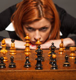 Geschäftsfrau, die an ihren nächsten Schritt in einem Spiel des Schachs denkt Lizenzfreie Stockbilder