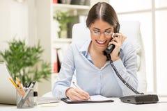 Geschäftsfrau, die im Büro anruft Stockfoto