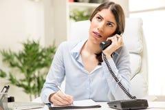 Geschäftsfrau, die im Büro anruft Lizenzfreie Stockfotografie