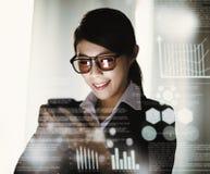 Geschäftsfrau, die im Büro arbeitet und in Verbindung steht stockfotografie