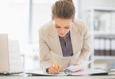 Geschäftsfrau, die im Büro mit Dokumenten arbeitet Stockfotos