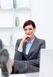 Geschäftsfrau, die im Büro mit Füßen auf Schreibtisch sitzt Stockbilder