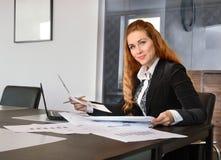 Geschäftsfrau, die im Büro mit Papieren arbeitet Stockfotografie