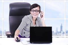 Geschäftsfrau, die im Büro unter Verwendung des Telefons und des Laptops plaudert Stockbild