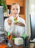 Geschäftsfrau, die im Büro zu Mittag isst Stockbilder