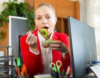 Geschäftsfrau, die im Büro zu Mittag isst Stockbild