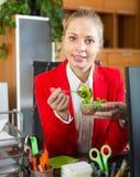 Geschäftsfrau, die im Büro zu Mittag isst Lizenzfreies Stockfoto