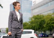 Geschäftsfrau, die im Bürobezirk steht Lizenzfreie Stockbilder