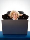 Geschäftsfrau, die im Lehnsessel durch den Laptop sitzt stockfotografie