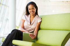 Geschäftsfrau, die im modernen Büro unter Verwendung Digital-Tablette sitzt Lizenzfreie Stockfotografie