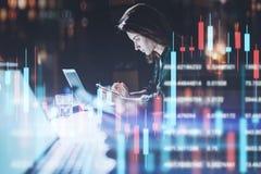 Geschäftsfrau, die im Nachtbüro in der vorderen Laptop-Computer mit Finanzdiagrammen sitzt und ihren Smartphone verwendet Rot und stockbilder